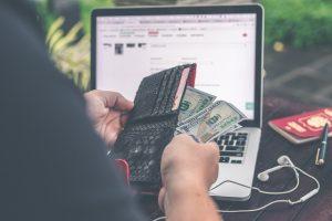 Mężczyza siedzący przed komputerem z pieniędzmi w ręce