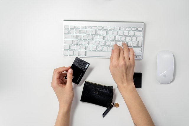 Człowiek krzymający kartę kredytową i piszący na klawiaturze