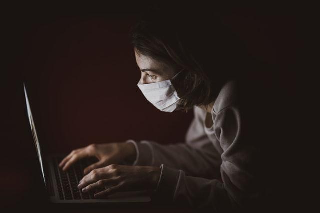 Kobieta w maseczce przed komputerem
