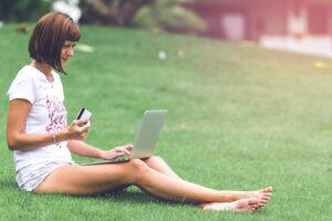 Kobieta trzymająca kartę kredytową i laptop