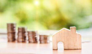 monety i mały, drewniany domek