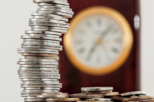 wysoka wieża z monet w tle zegarek